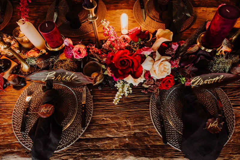 Dining table set for a bride and a groom, styled with red roses and smaller, rustic blooms among dark red candles and golden candlesticks