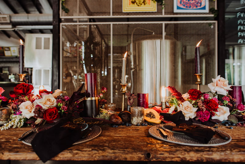 Cozy, rustic darker themed floral tablescape in the foreground of Little Island Brewing Co at Changi Village