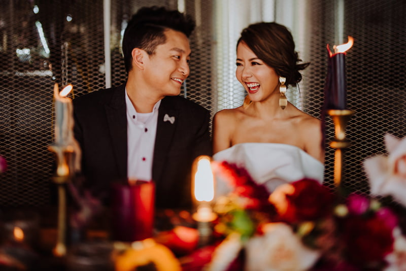 Wedding couple seated behind a wine red, dark floral tablescape and candles