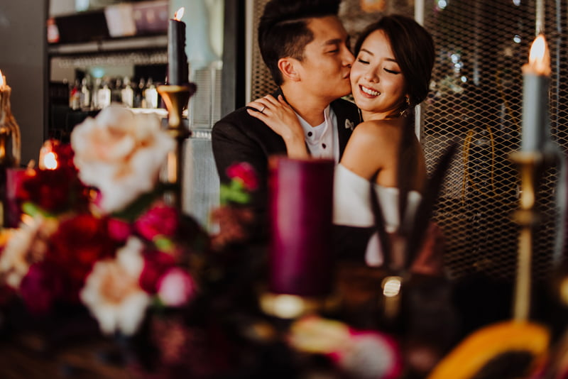 Groom kissing the bride, seated in front of lavish blooms arranged for a wedding dinner table party