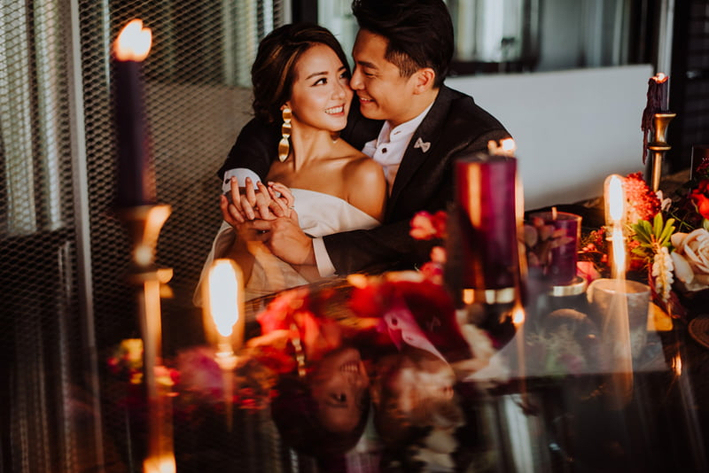 Bridal couple looking lovingly at each other, seated at arranged table with floral centrepieces and burgundy candles