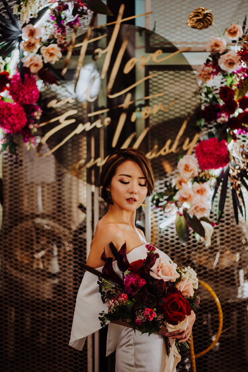 Bride looking down at dark red roses in a mid-sized bridal bouquet, standing in front of brewing vats at Little Island Brewing Co.