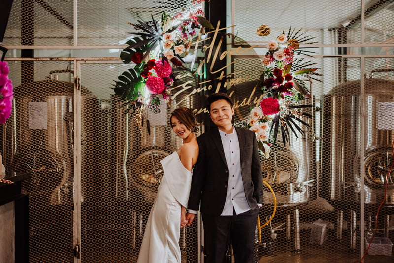 Wedding couple styled in front of dark colour orchids, tropical leaves and fronds, roses arranged in front of beer brewing vats at Little Island Brewery Changi Village