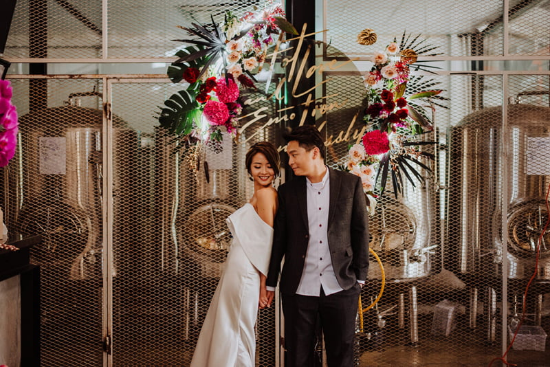 Bride in avant-garde strapless wedding jumpsuit and low bun, groom in casual suit in front of beer brewing machines