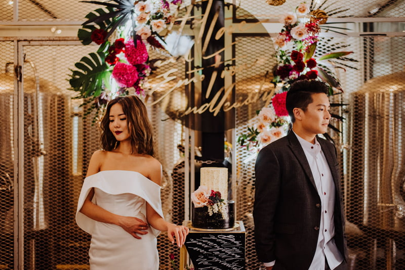 Couple in casual wedding outfits in front of suspended flower arrangement at Changi Village venue