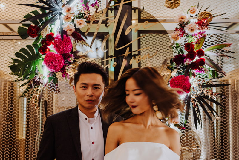 Motion shot of bride and groom, posed in front of flower installation in theme with an adventurous wedding venue at Little Island Brewing Co Changi Village