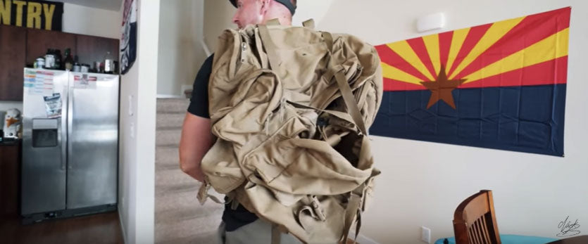 Soldier Puts on Ruck Sack