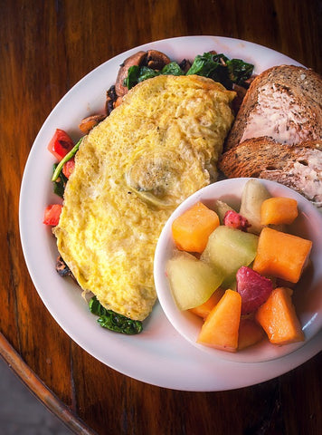 Plate holding vegetable omelet, toast, and cup of fruit.