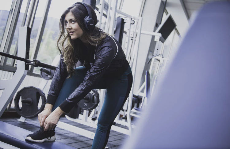 Woman ties her shoe will listening to music on her gym workout app.