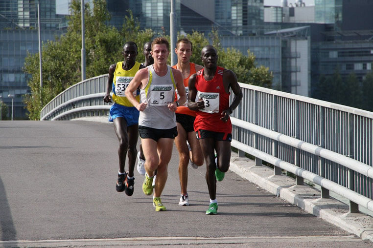 Group of Male Marathon Runners Run Over Bridge