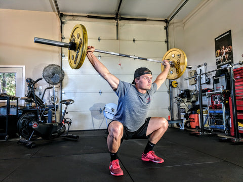 Man squatting while holding a barbell over his head.