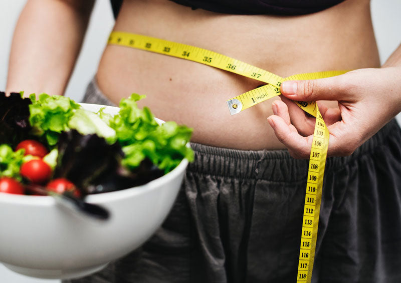 holding salad while measuring stomach