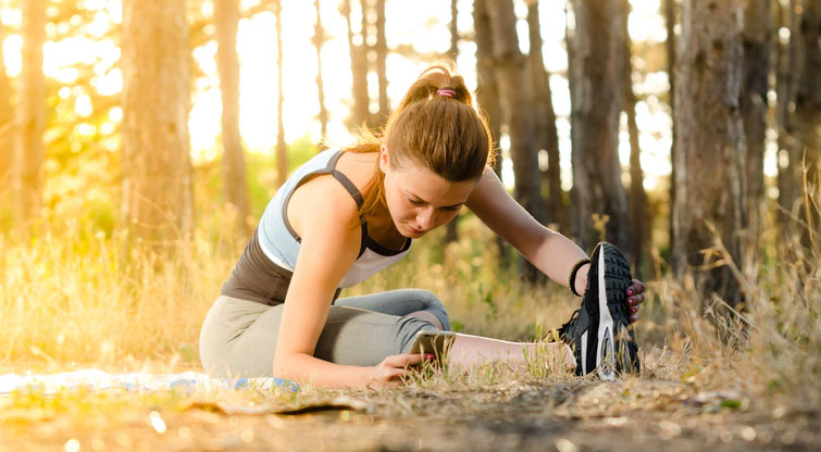 Woman looks at her weight lifting app while stretching during a run.