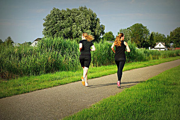 Two women jogging through the park