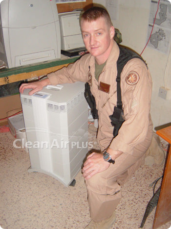 Marine standing next to IQAir purifier donated by Clean Air Plus.