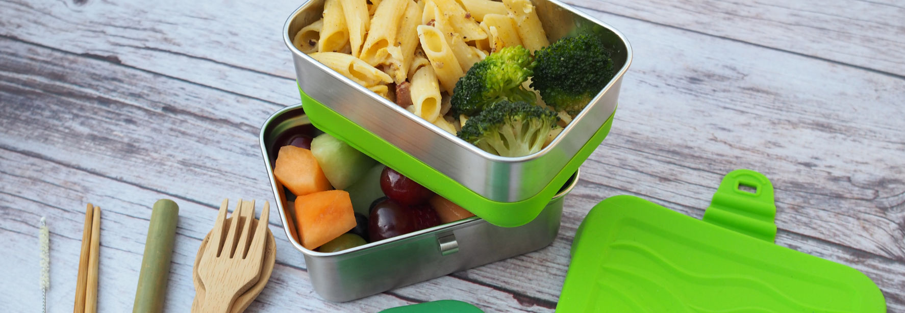 ECOlunchbox Blue Water Bento containers holding pasta, broccoli, and fruits on a table with reusable forks and straws.