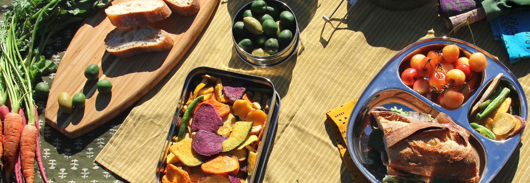 Stainless steel containers and wood serving board with fruits, veggies, and a sandwich laying on colorful picnic blankets.