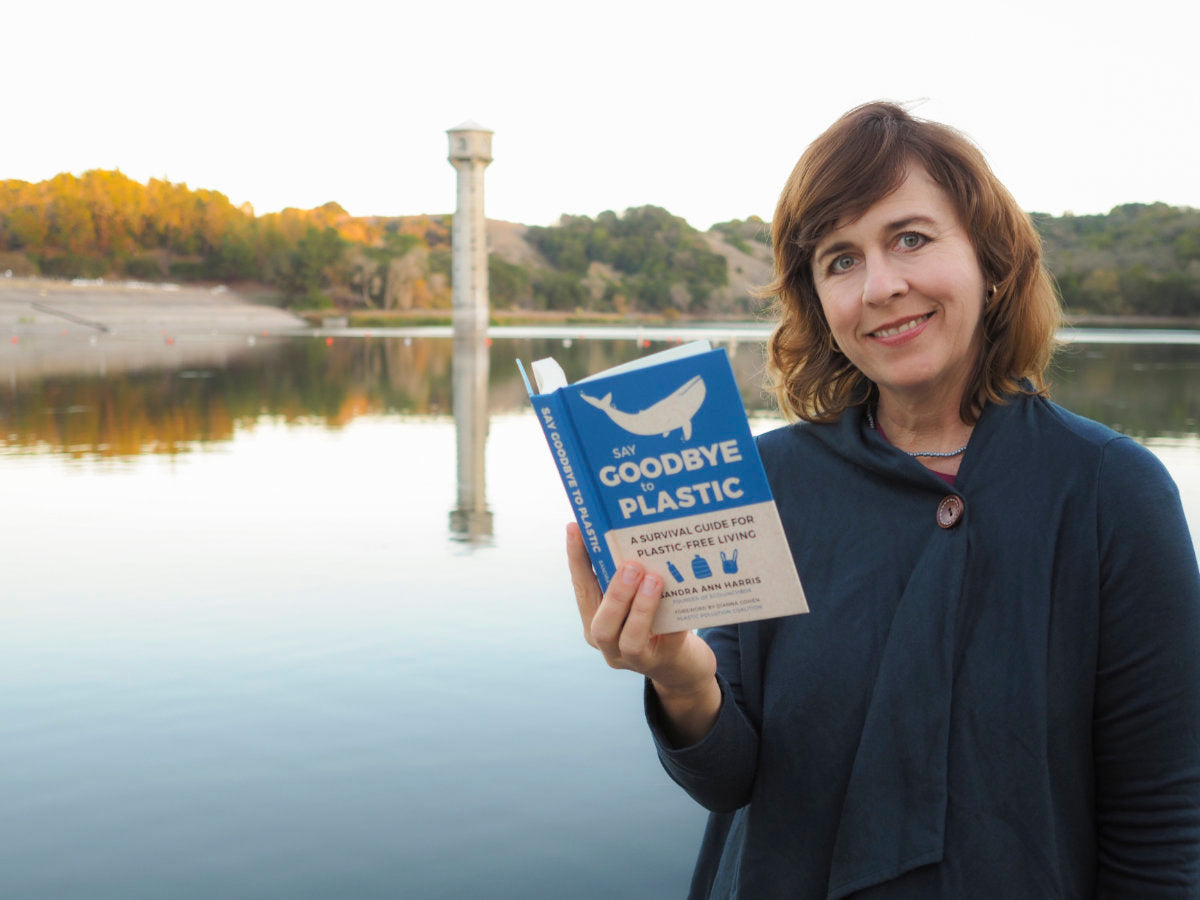 Sandra Ann Harris outside near a water reservoir holding a copy of her book, Say Goodbye to Plastic