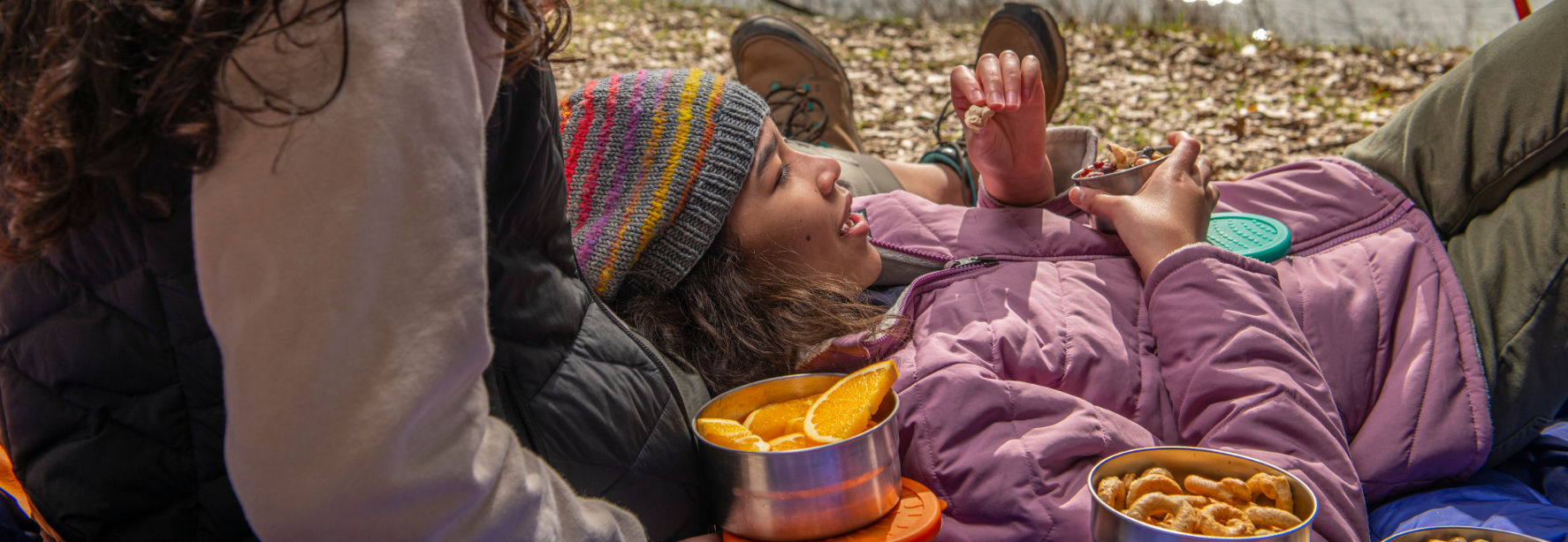 Girl in a beanie and sweater vest laying with a friend by a lake with healthy snacks in ECOlunchbox containers.