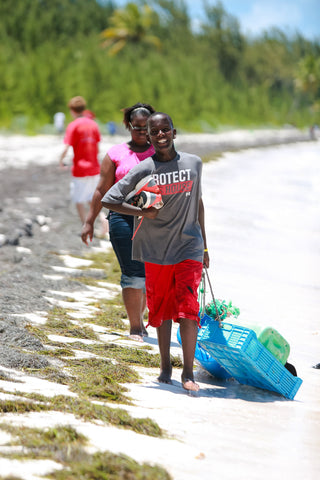 Students collect and remove plastic debris and other trash during a  beach clean-up in the Bahamas