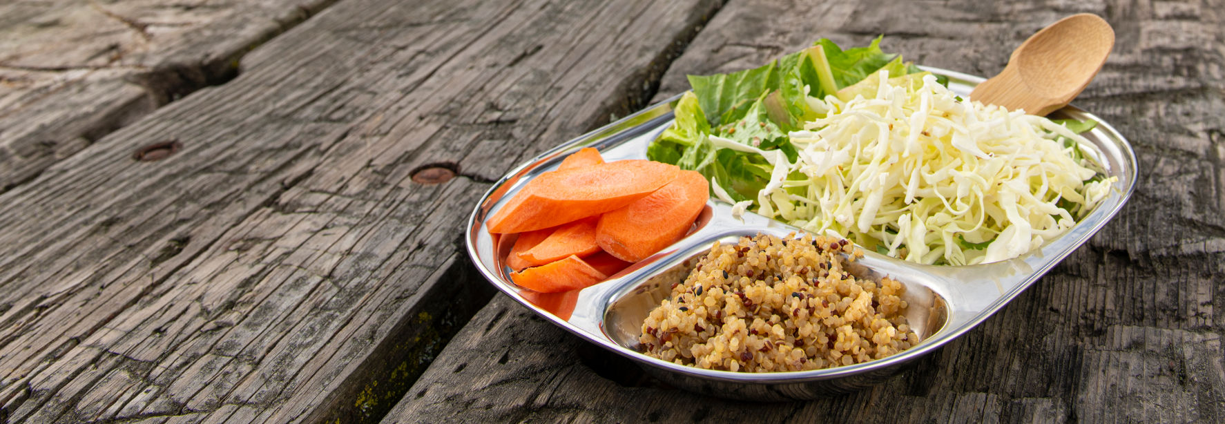 ECOlunchbox tray with cabbage, lettuce, carrots, quinoa, and wood spork on rustic park bench.
