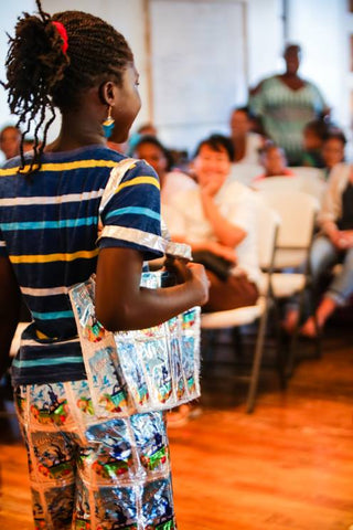 "PHOTO: Upcycling plastic into clothing and accessories is just one of the activities the students participate in. Here, a camper named Donniqua models her handmade ""Trashion Fashion"" at the camp's community show."