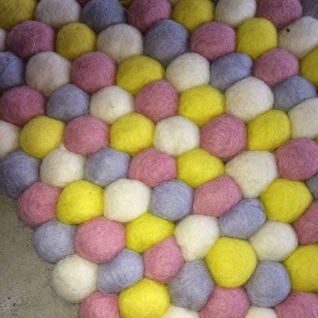 yellow and pink felt ball rug