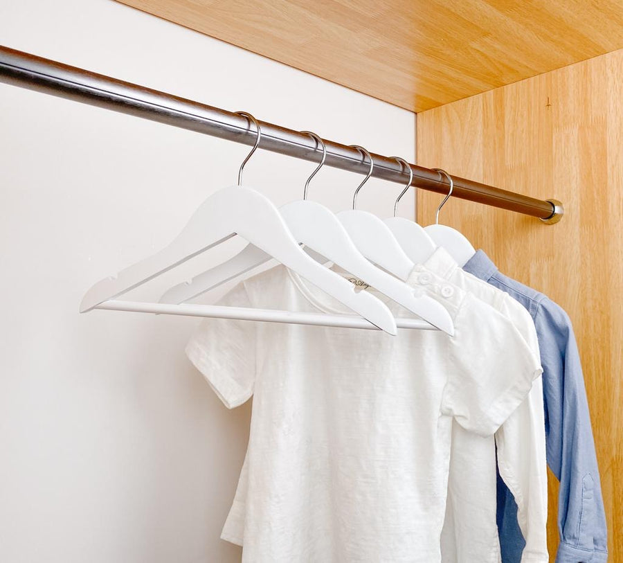kids clothes hung on white kids wooden hangers, white shirt and blue shirt on children white wood hangers