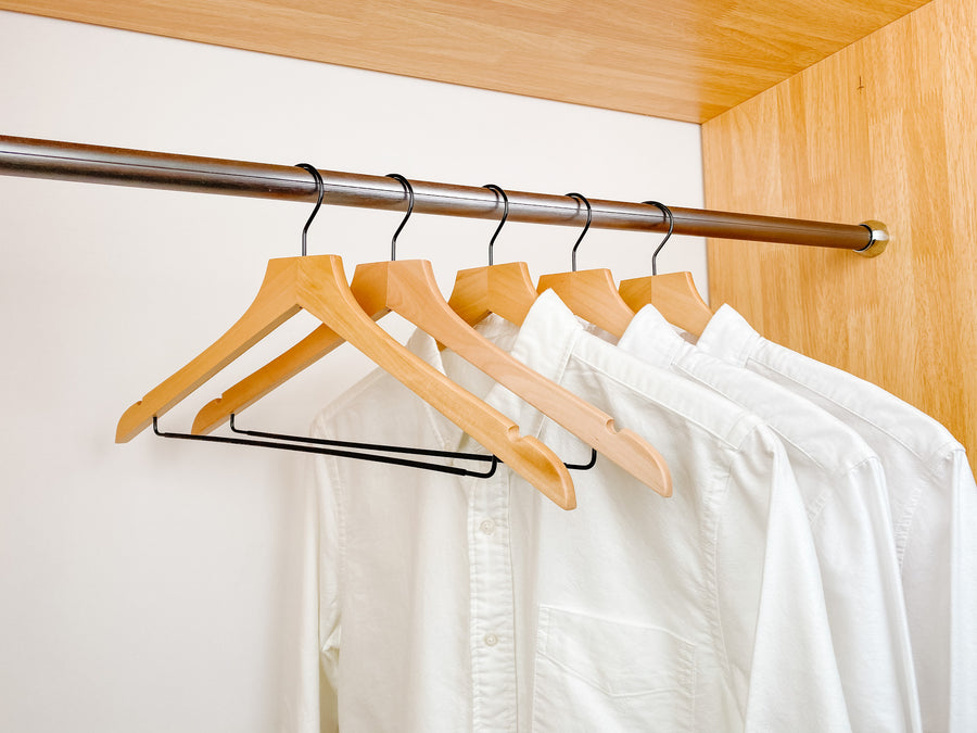 white shirts hung on a modern natural wooden hangers with black chrome non slip pant bar and black chrome 360 degree hook, minimalist capsule wardrobe design with natural hangers with black chrome hardware.