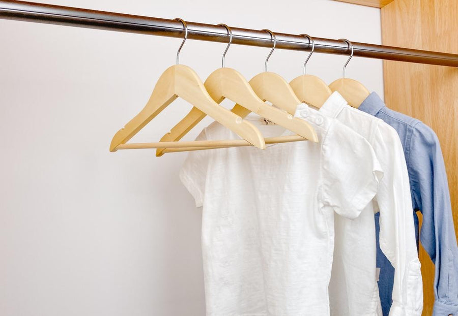 kids clothes hung on natural kids wooden hangers, white shirt and blue shirt on children natural  wood hangers