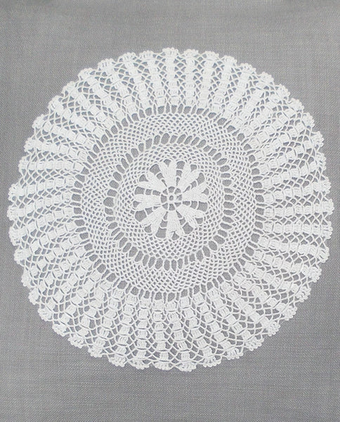 Linen cushion cover with crochet doily, closeup view
