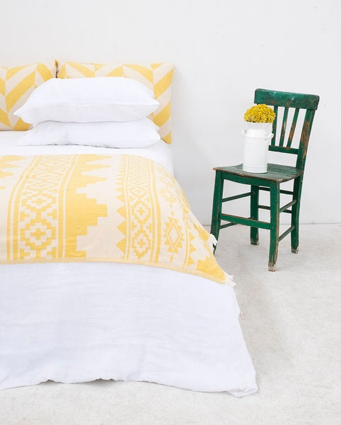 Yellow throw in bedroom setting