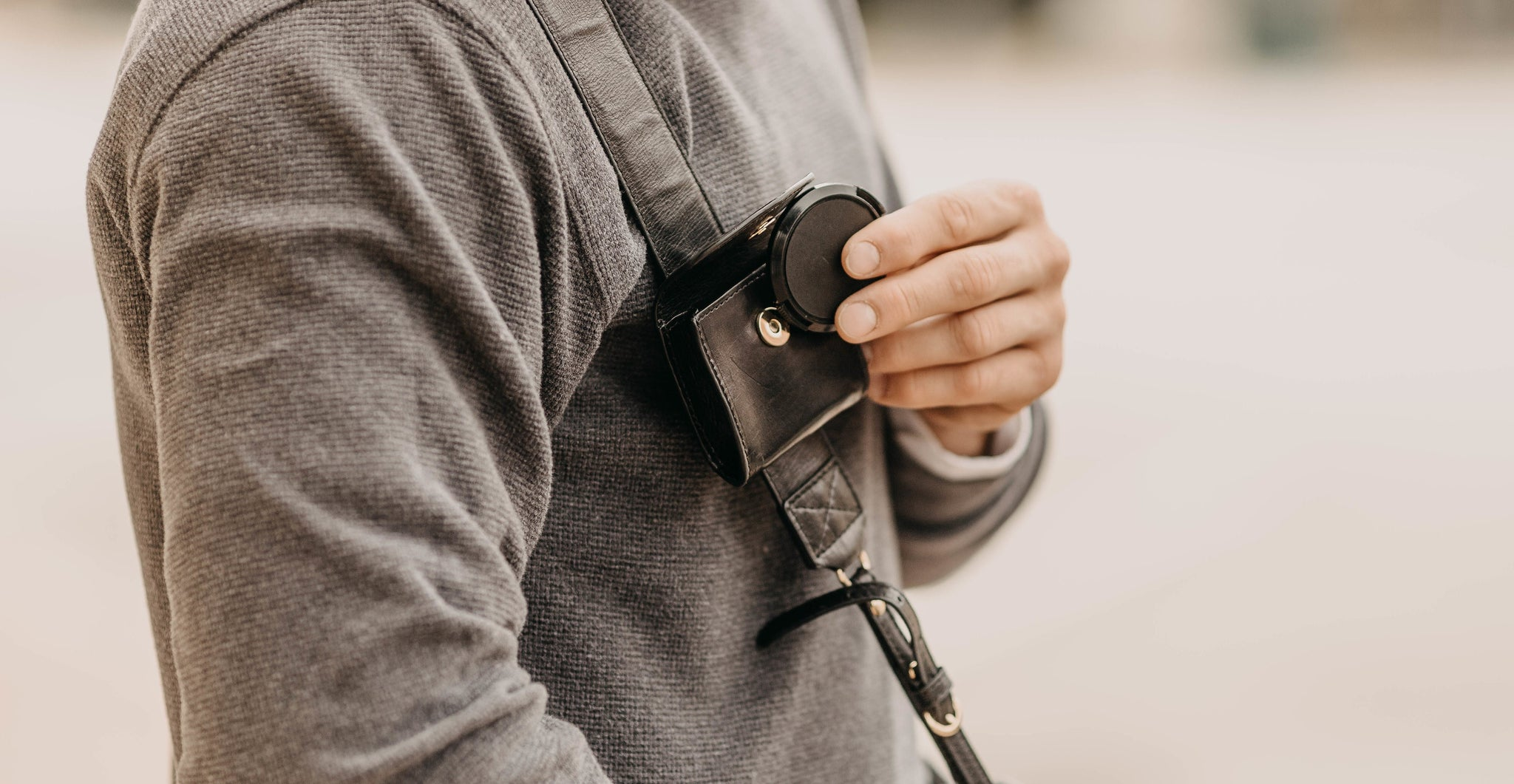 Black leather camera strap with a monogram