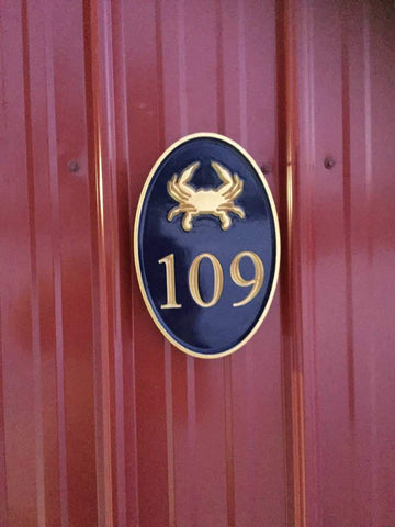 blue and gold oval house number sign with crab