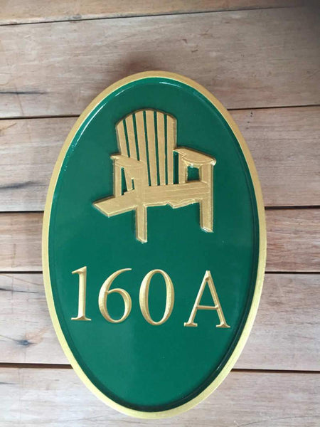 Green and gold house number sign with adirondack chair