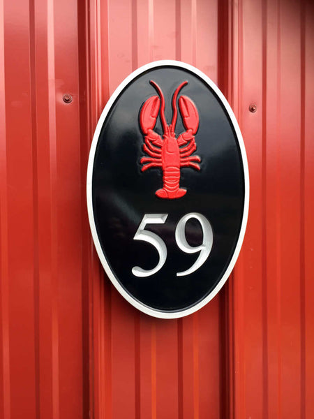 oval house number sign with red lobster and silver number and border.