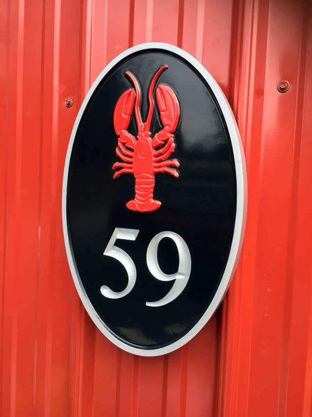 Side view of oval house number sign with red lobster and silver number and border.