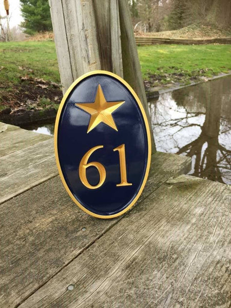 House number sign with 61 and patriotic star painted navy blue and gold.