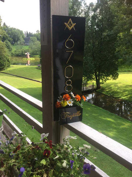 black and gold vertical house number sign with last name and flower box