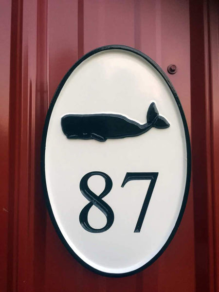 oval house plaque painted black and white with whale image