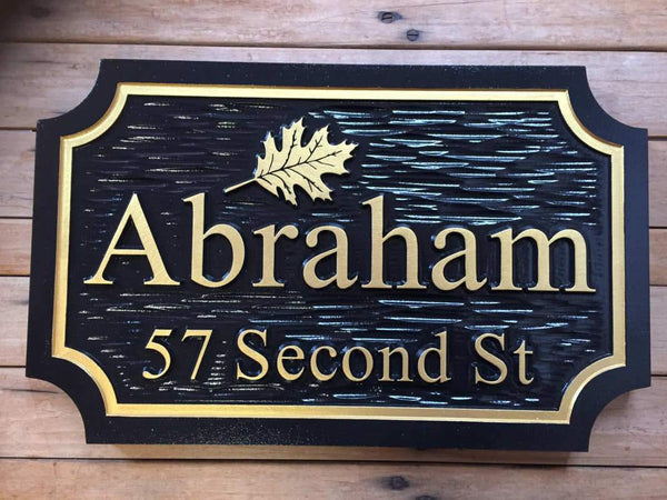 Last name sign with oak leaf image and address painted black and gold