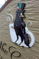 Close of up crow artwork carved on ornate shaped coffee shop sign with business name
