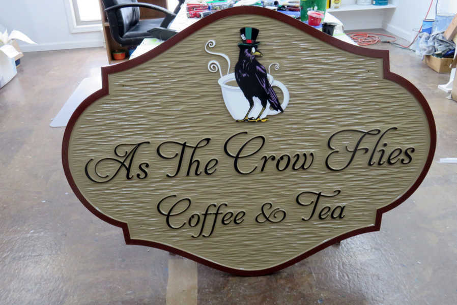 Ornate shaped coffee shop sign with business name and crow carved and painted on it