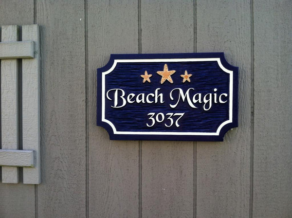 Custom carved rectangle sign with notched corners with house name and starfish and address carved on it with chiseled background.