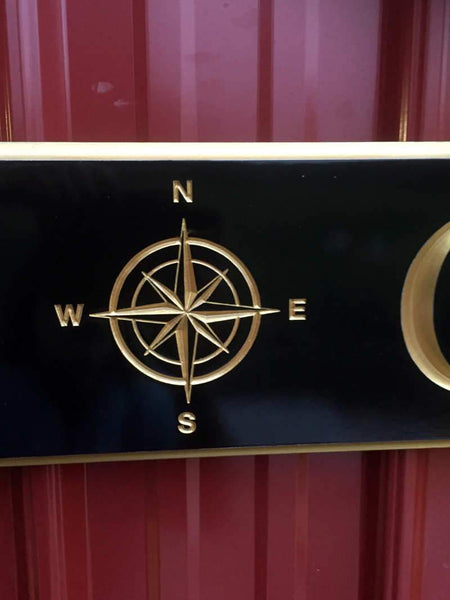 Close up of personalized quarterboard sign with compass rose image in center painted black and gold