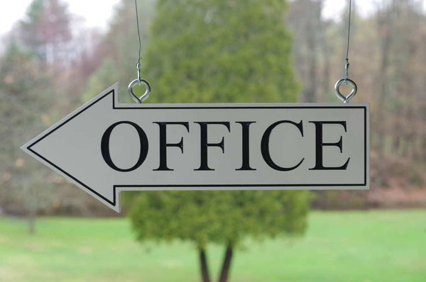 Directional arrow office sign hanging from eye screws.