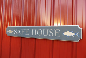 Quarterboard sign with Safe House and sharks carved on it
