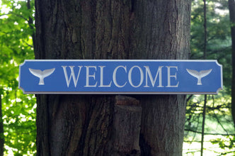 Welcome sign with whale tail images