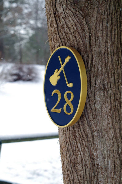 Side view of custom carved house number sign with electric guitar and golf club