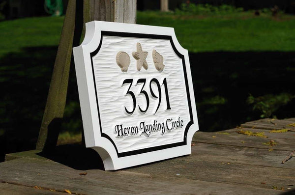 Side view of custom carved address sign with sea shells painted white with black and taupe trim